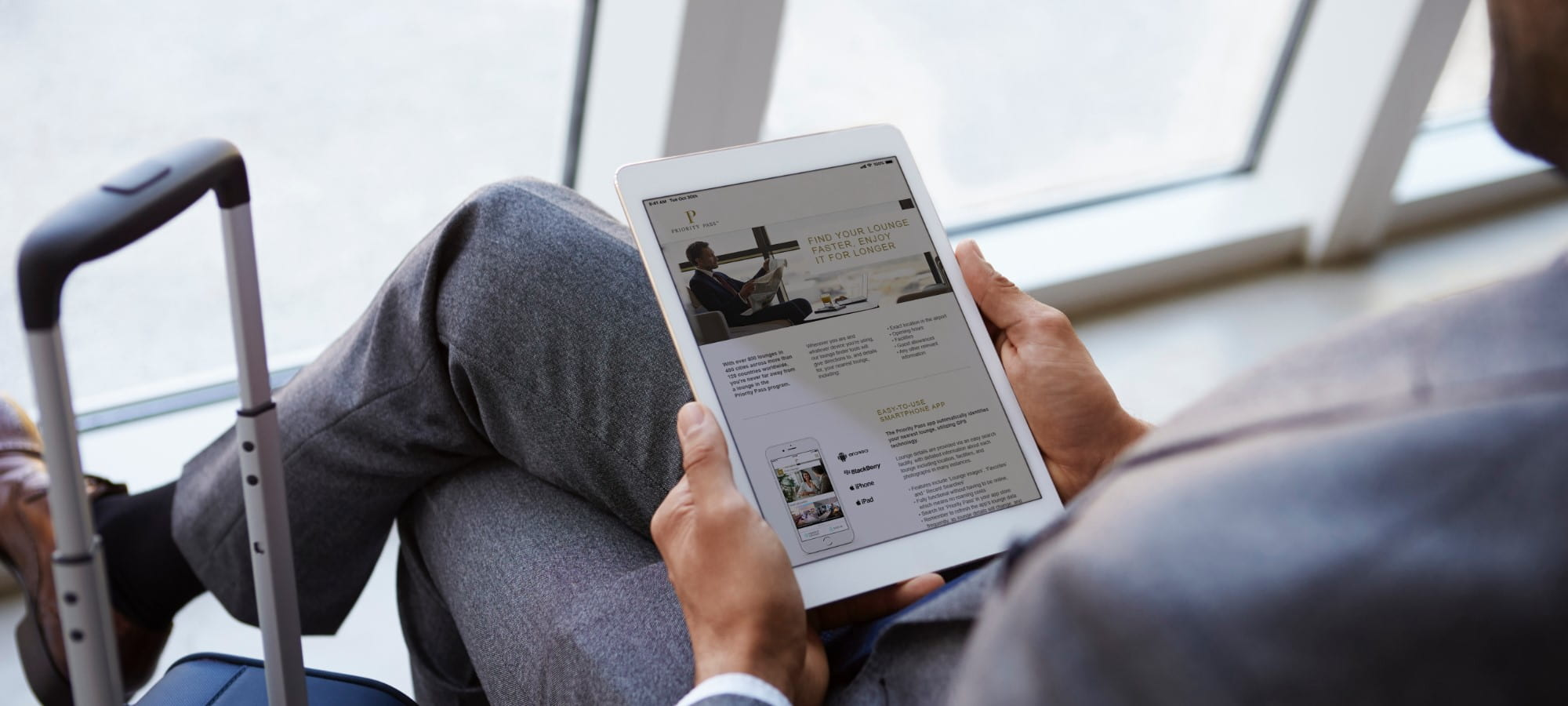 Man reading priority pass website on tablet in airport lounge